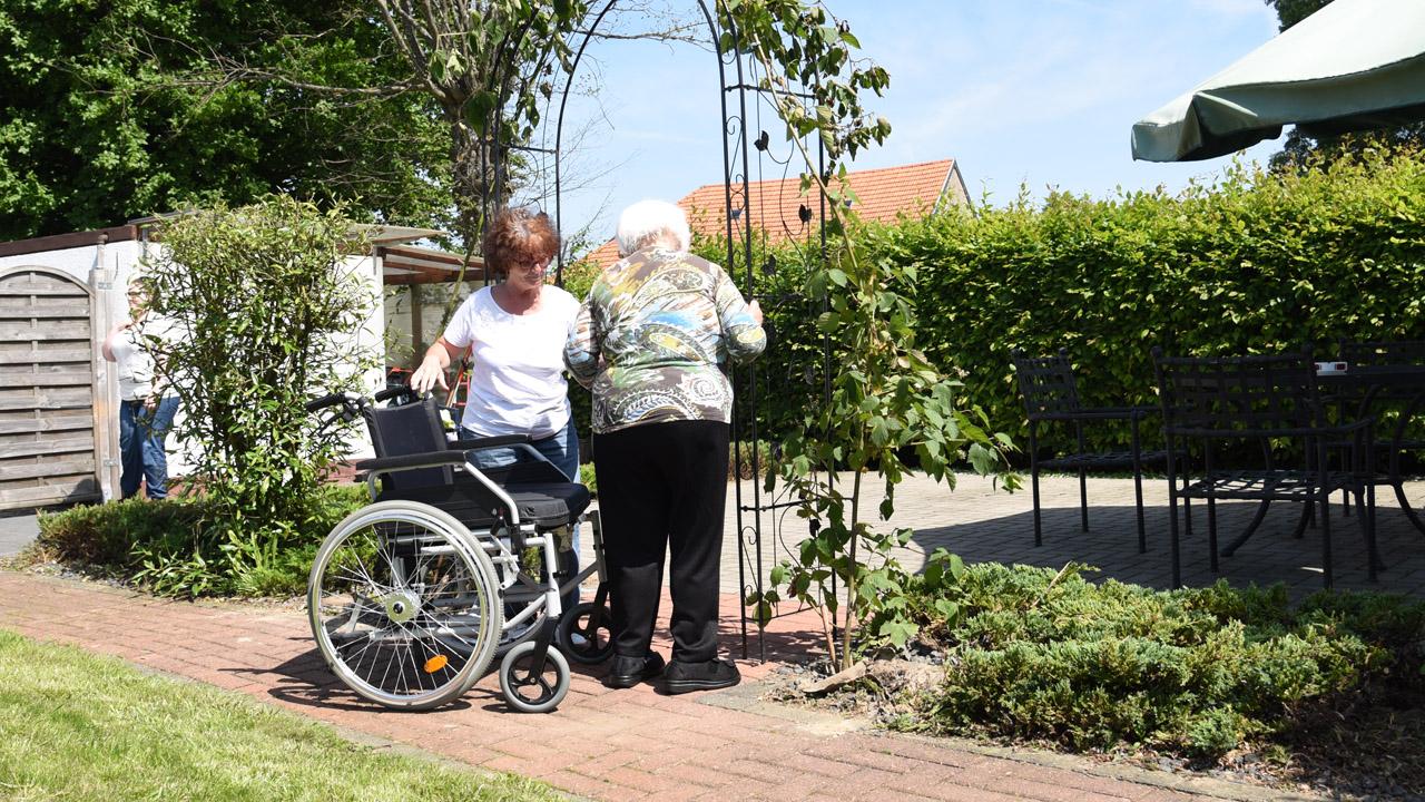 Krankenpflegerin hilft Bewohnerin in den Rollstuhl.