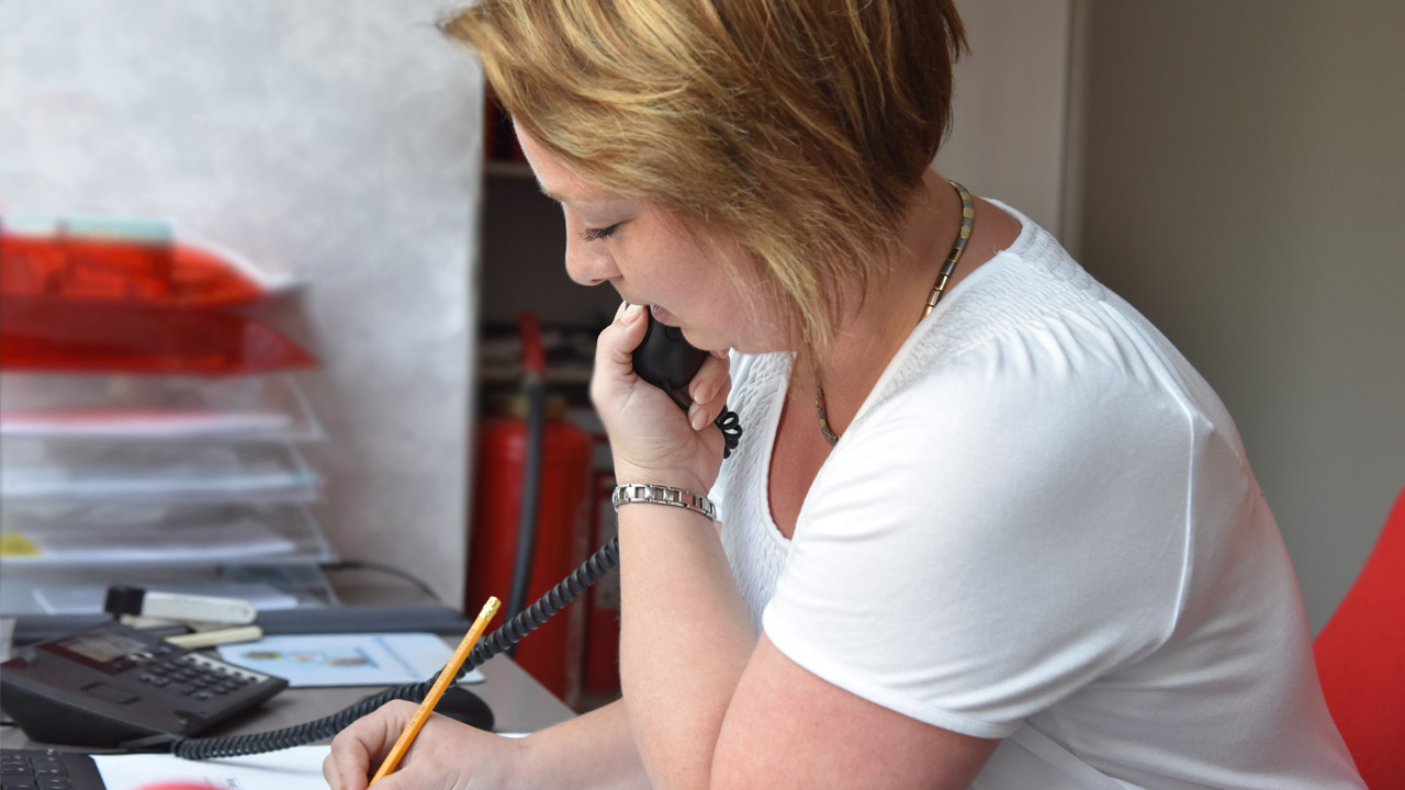 Mitarbeiterin koordiniert Kundenanfragen am Empfang.