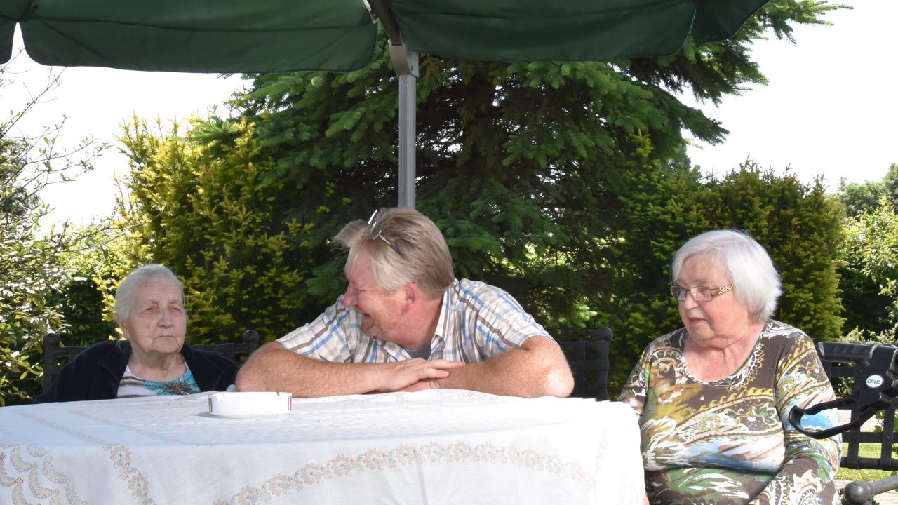 Herbert mit zwei Seniorinnen im Garten unter dem Sonnenschirm.